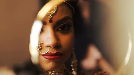 prepairing : Gorgeous Indian bride looks at her reflection in the mirror