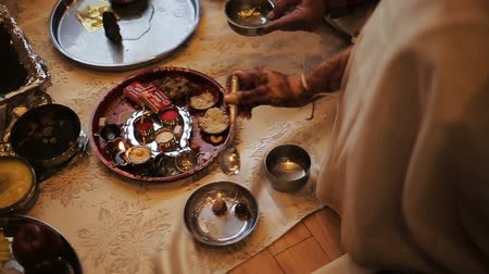 sherwani : Hindu woman pours water from the spoon over the nuts in silver plate