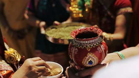 sherwani : Woman gives something to taste for man while he holds a red bowl