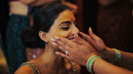 sherwani : Indian bride smile while woman covers her face with haldi