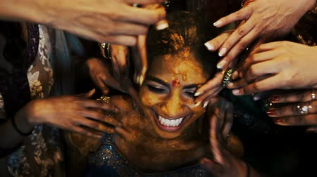sherwani : Indian brides face covered with turmeric paste by other women