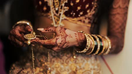 prepairing : Red and golden bracelets over the hands of Indian bride