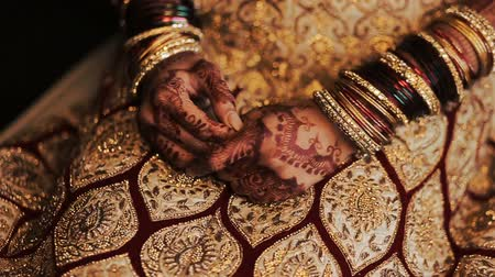 prepairing : Red and golden bracelets put over the hands of Indian bride