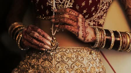 prepairing : Indian brides holding a golden pendant hanging over her red costume Stock Footage