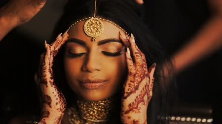 prepairing : Alluring Indian bride holds her delicate fingers behind her temples while women get her hair ready