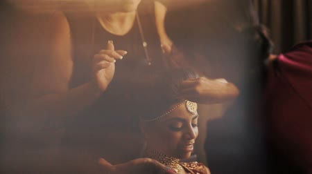 prepairing : Woman adjusts makeup on stunning brides face while she sits calm on the chair