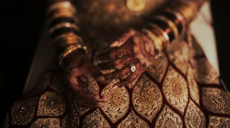prepairing : Closeup of Indian brides hands covered with mehndi and holding a golden necklace Stock Footage