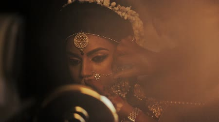 prepairing : Morning light illuminates Hindu bride while she looks in the mirror Stock Footage