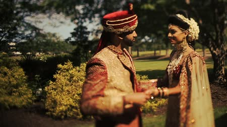 sherwani : Tall groom in red traditional wedding hat looks at a gorgeous Indian bride