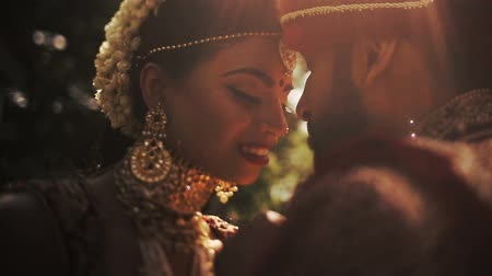 sherwani : Delightful Indian bride holds her grooms hand while leaning her forehead with his