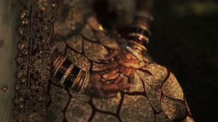 prepairing : Shadows lie over the knees of Hindu bride dressed in golden clothes