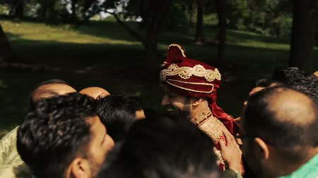 bengali : Handsome groomsmen surround attractive Indian groom while standing in the garden