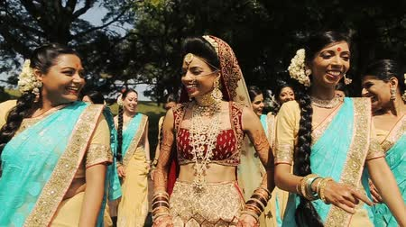 prepairing : Stunning Indian bride in red wedding suit walks with her bridesmaids in blue sarees
