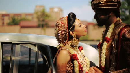 sherwani : Groom looks in beautiful brides eyes while they stand by the car