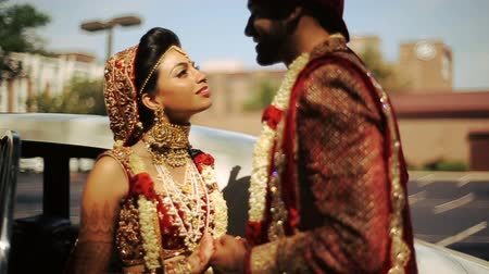 sherwani : Bride and groom look in each other eyes while they stand by the car