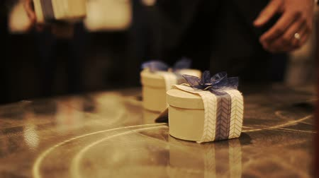 sherwani : Little present boxes decorated with blue ribbons stand on the wooden table Stock Footage