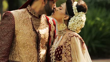 sherwani : Dreamy Indian bride leans to her tall groom for a kiss Stock Footage
