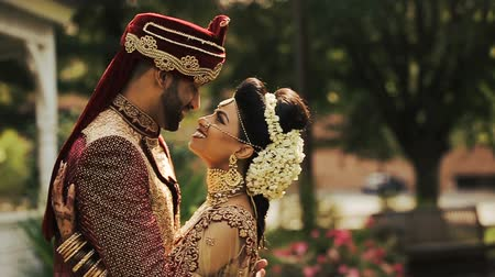 sherwani : stylish Indian bride and her handsome groom sharing a warm hug