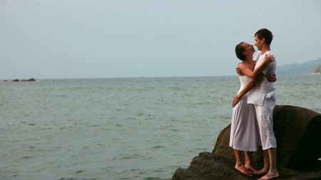 casal heterossexual : Kissing couple on a rock in a ocean.