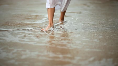 giydirmek : Woman walking on a sandy ocean beach.