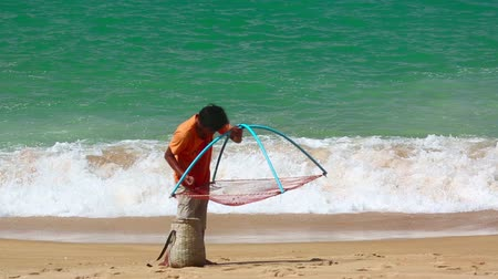 krewetki : PHUKET, THAILAND - NOVEMBER 28, 2014: Unidentified man catches of shrimp in coastal waves on Nov.28, Mai Khao beach, Phuket, Thailand