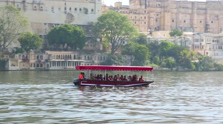 pichola : UDAIPUR INDIA  November 23 2012: Unidentified tourists take boat ride in front of City Palace on February 8 2011 in Udaipur India.
