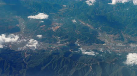 jet out : Beautiful view through airplane window, airplane flying above city in mountains Stock Footage