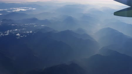 jet out : Beautiful view through airplane window, airplane flying above river in mountains Stock Footage
