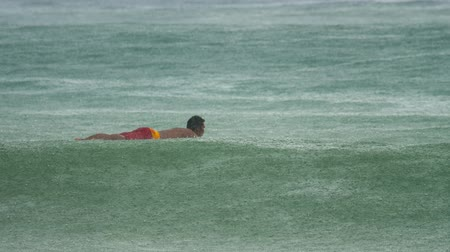 extreme weather : Surfer on the waves at havy rain
