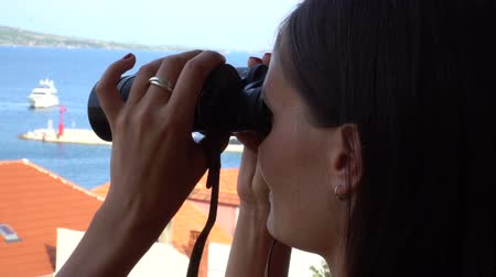 looking far away : Woman looking through binoculars at sea