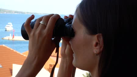 looking far away : A woman looking through binoculars Stock Footage