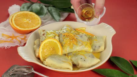 mártás : Orange sauce being poured over chocolate crepe suzette followed by brandy over the top.  Stock mozgókép