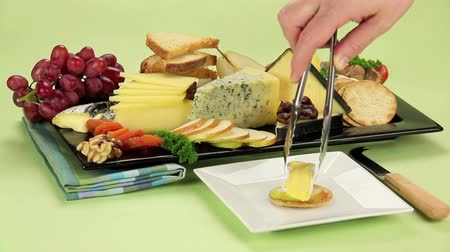 fresh cheeses : Delicious cheese platter with various cheeses and fruits being served on to a plate Stock Footage