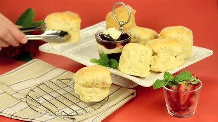 scones : Hot scones straight from the oven being put on to a tray with a pair of tongs.