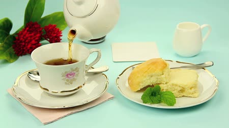 scones : A cup of tea being poured then jam and cream being spread on a scone.