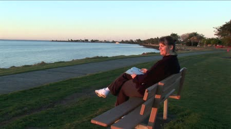livro : Middle aged woman reading a book at sunset in front of a quiet bay.  Vídeos