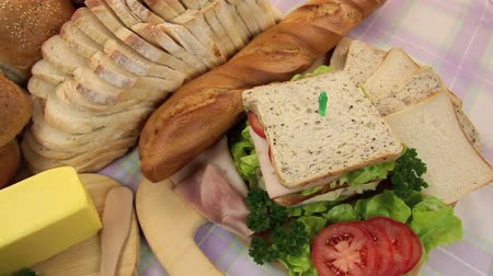 delicioso : Dolly across different breads and rolls revealing a tasty fresh made salad sandwich.
