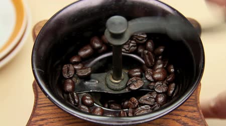 caffe : Freshly roasted coffee beans being ground in an old fashioned coffee grinder. Stock Footage