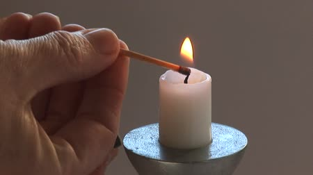 tektura : Close up of match being struck against a match box then lighting a candle.