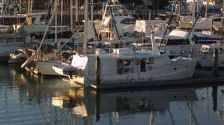 cascos : Zoom back from a boat to reveal yachts and boats at rest in a marina at sunset.