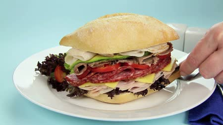 placas : Mega meat roll with assorted meats being put on to a plate with a spatula.