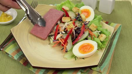 ovo : Slices of spam being served on to a plate with a salad.