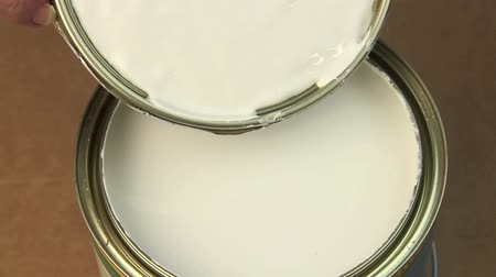 undo : Taking the lid off a can of paint with a screwdriver then stirring with a wooden spoon.