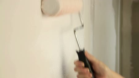 malarstwo : Painting out a bare wall with a paint roller with white paint.