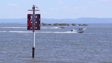 speedboats : Two speed boats pass behind a red beacon on open water.