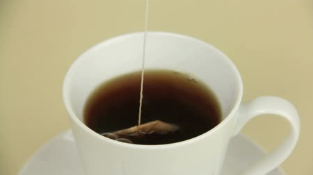 tea bag : Boiling water in a an electric jug then dipping a tea bag in a mug.