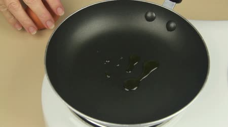 kızartma : Olive oil poured into frypan then an egg is cracked and put in. Stok Video