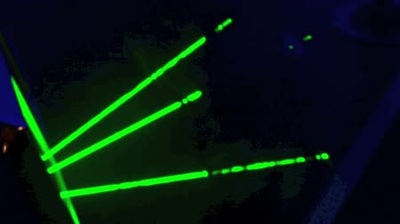 light amplification : Green laser light flashing on a dark background.