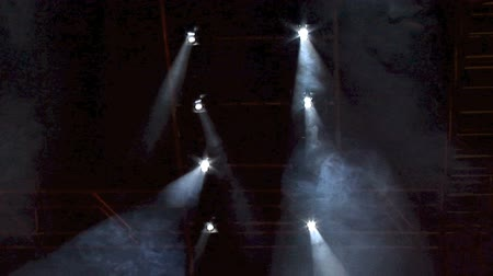 light amplification : Spot lights shining through clouds of smoke from the ceiling of a rock concert. Stock Footage