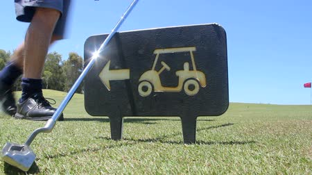 kurs : A golf iron is picked up as a player walks by a golf buggy sign on a golf course.